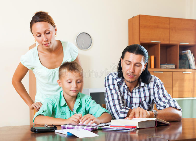 Smiling parents helping with homework. Parents and teenager helping with homework in home interior royalty free stock images