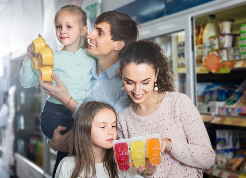 Smiling parents with two kids holding purchases in store. Average smiling parents with two kids holding purchases in store stock photos