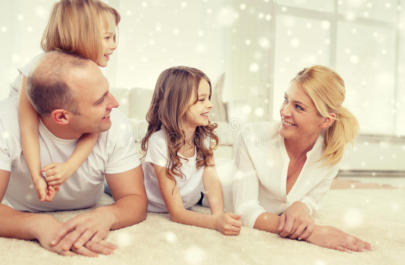 Smiling parents and two little girls at home royalty free stock photography