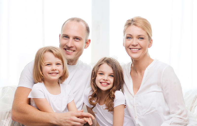 Smiling parents and two little girls at home royalty free stock image