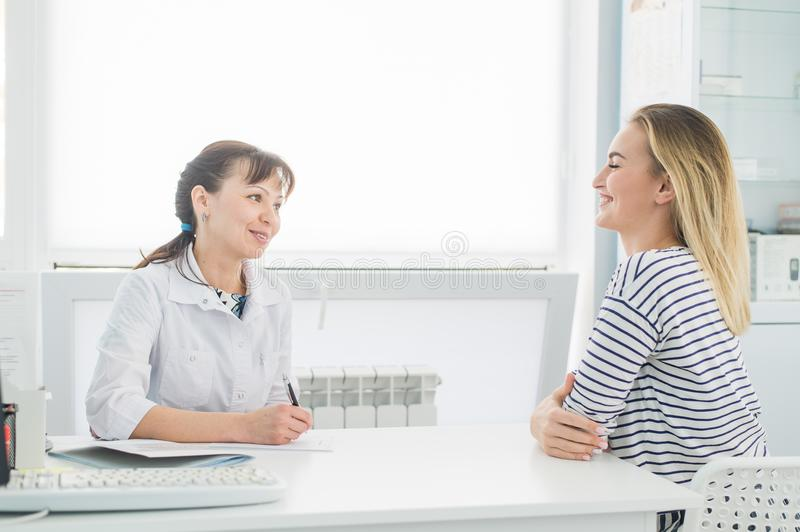 Smiling patient receiving a medical consultation and looking at camera, the female doctor is sitting at desk on the stock photography