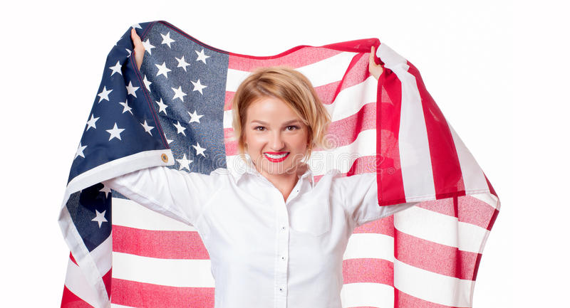 Smiling patriotic woman holding United States flag. USA celebrate 4th July. American flag. Smiling patriotic woman holding United States flag. USA celebrate 4th royalty free stock photography