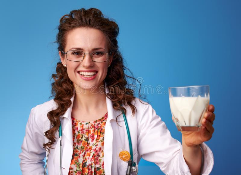 Smiling pediatrist doctor giving glass of milk on blue stock photography