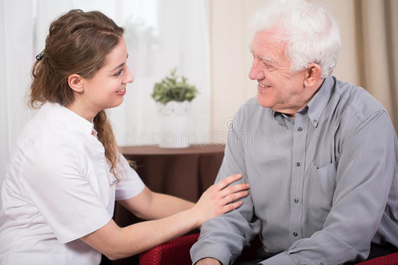 Smiling pensioner and caregiver royalty free stock images