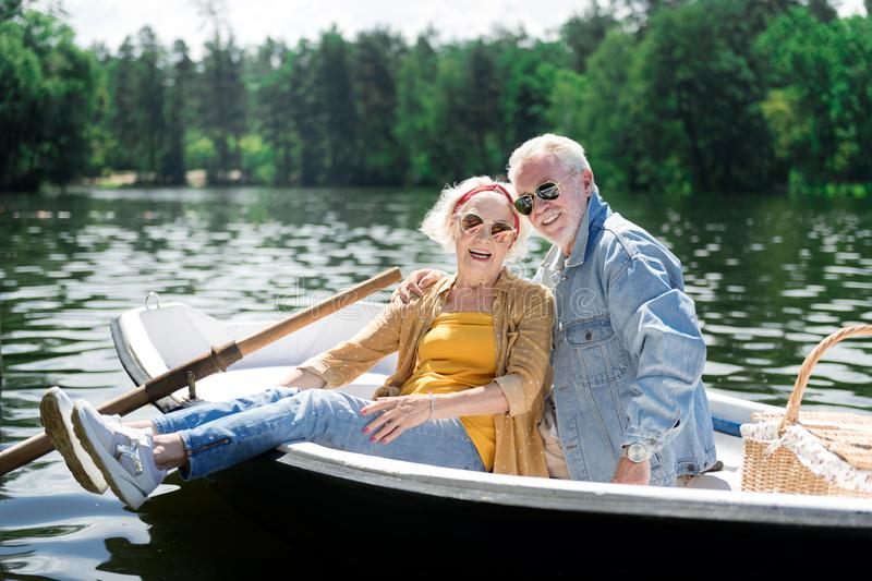 Smiling pensioners sitting in little boat while having romantic date royalty free stock photography
