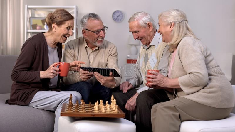 Smiling pensioners watching online video tablet together, playing chess, hobby royalty free stock image