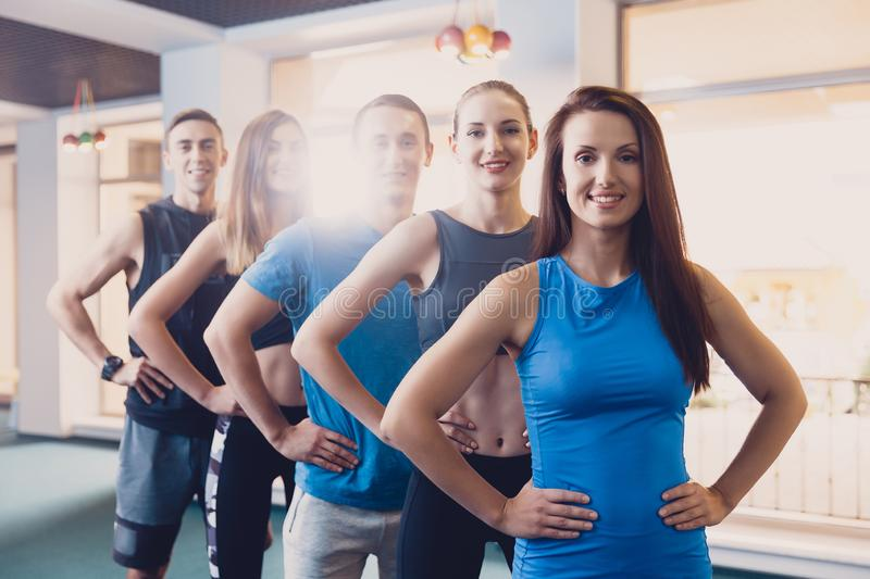 Smiling people doing power exercise fitness studio. A small group of men and women warming up before an upcoming workout. Sports people do workout between stock image