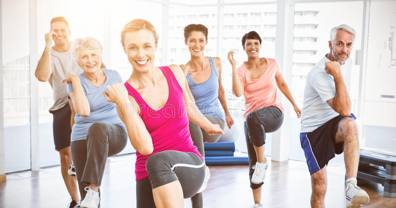 Smiling people doing power fitness exercise at yoga class royalty free stock images
