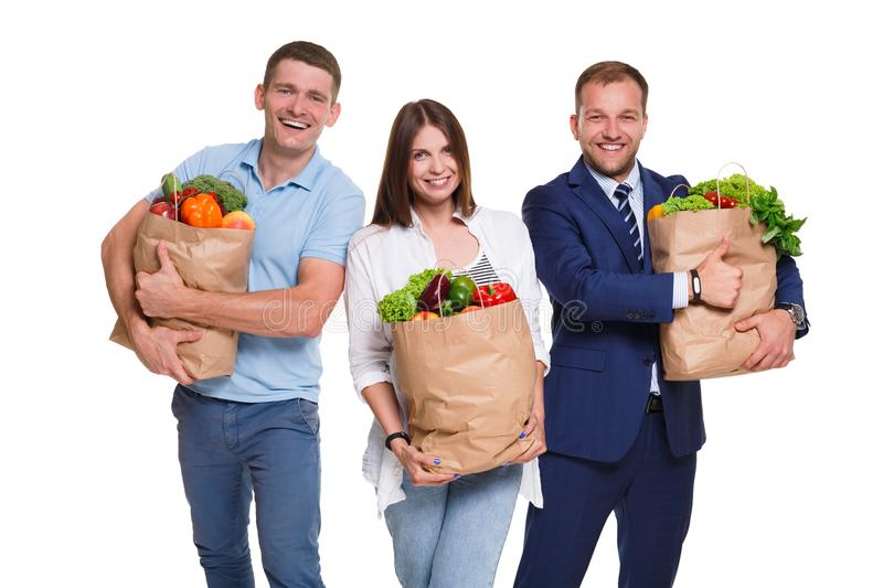 Smiling people holding shopping bags full of vegetables isolated on white background. stock image