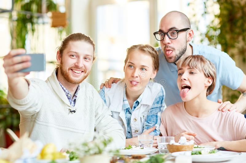 Friends taking selfie and grimacing in cafe stock images
