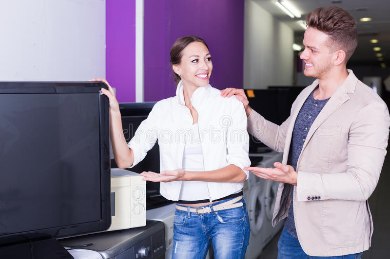 Smiling people purchasing flat screen television set stock photo