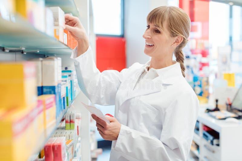 Pharmacist or Chemist woman sorting drugs in shelves in her pharmacy stock photos