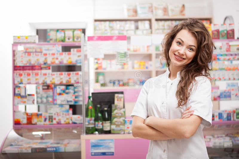 Smiling pharmacist in front of her desk at work royalty free stock photo