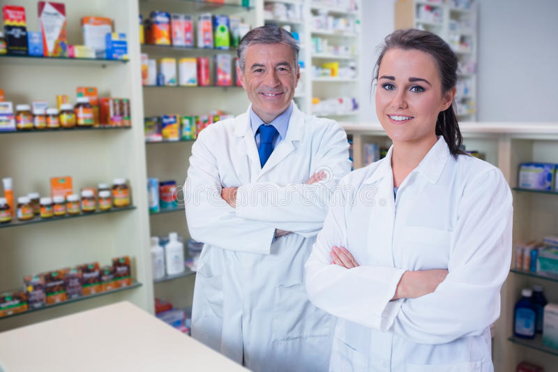 Smiling Pharmacist And His Trainee With Arms Crossed Stock Image ...