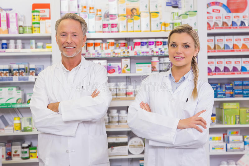 Smiling pharmacist and his trainee with arms crossed. In the pharmacy stock image