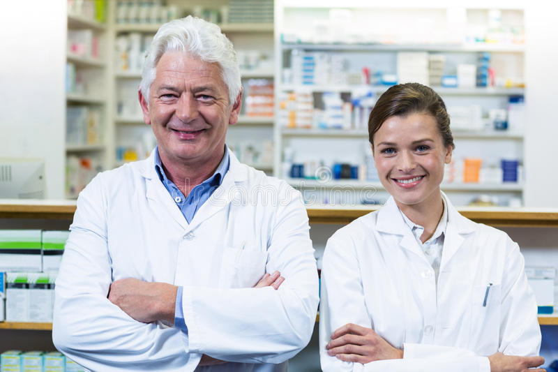 Smiling pharmacists standing with arms crossed in pharmacy. Portrait of smiling pharmacists standing with arms crossed in pharmacy stock photo