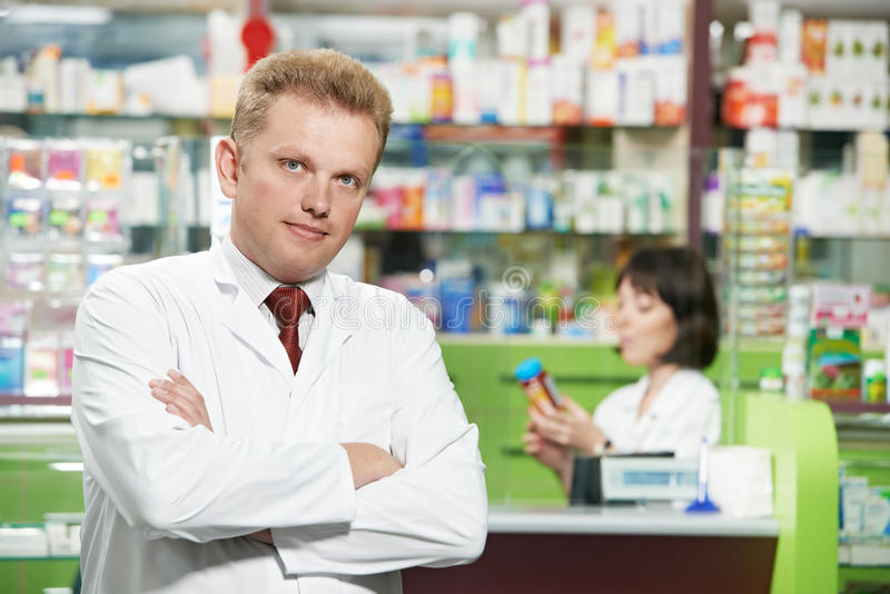 Smiling pharmacy chemist man in drugstore royalty free stock photos