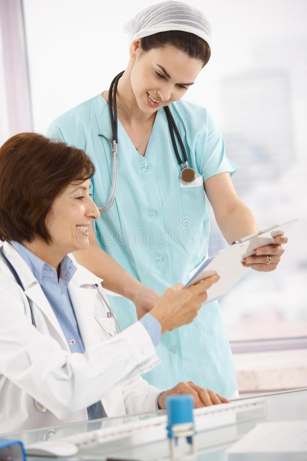 Smiling physician working with nurse stock image