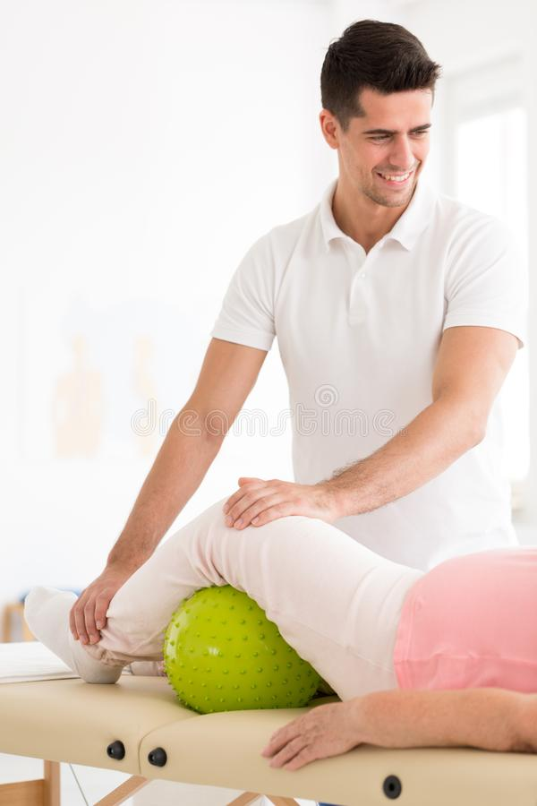 Smiling physiotherapist and elderly patient royalty free stock photography