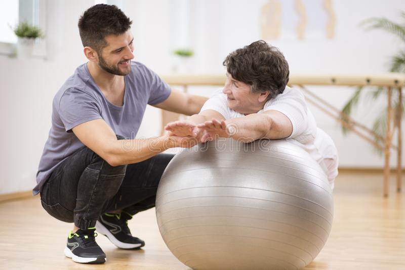 Smiling physiotherapist helping elderly patient stretch arms at the rehabilitation center. Smiling physiotherapist helping elderly patient stretch arms at the stock image