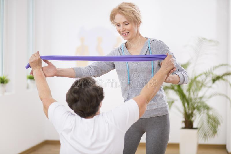 Smiling physiotherapist helping senior woman working out with resistance bands. Smiling physiotherapist helping senior women working out with bands royalty free stock images