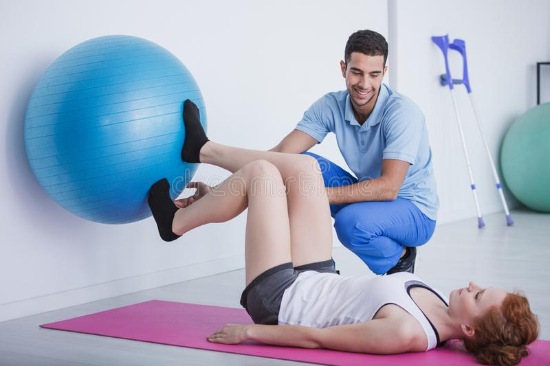 Physiotherapist supporting woman exercising with rehabilitation ball. Smiling physiotherapist supporting women exercising with rehabilitation ball royalty free stock image