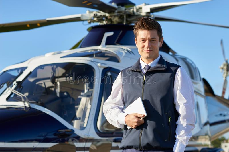 Portrait Of Pilot Standing In Front Of Helicopter With Digital T stock images