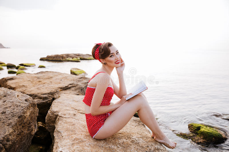 Smiling pin up girl reading book sitting on the rock stock photo