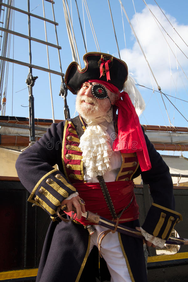 Smiling pirate with pirate ship. Happy smiling old pirate in colorful traditional costume stands on board ship and draws his sword. Square sail rigging and blue stock photography
