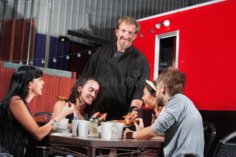 Canteen Owner with Happy Diners stock photos