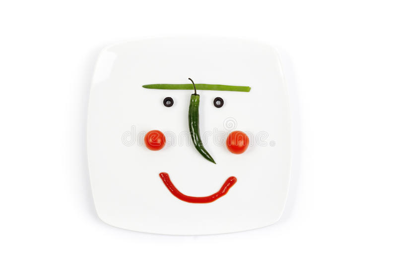 Smiling plate with a vegetable mug. A cheerful breakfast of the vegetarian royalty free stock image