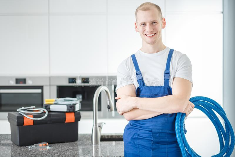 Smiling plumber with blue pipes royalty free stock image