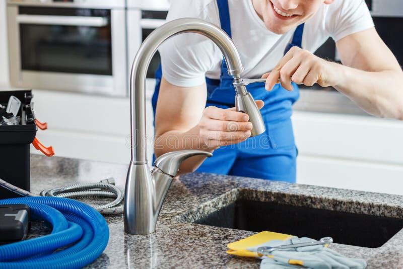 Smiling plumber fixing faucet. Close-up of smiling plumber fixing a faucet with blue pipes on the countertop stock image