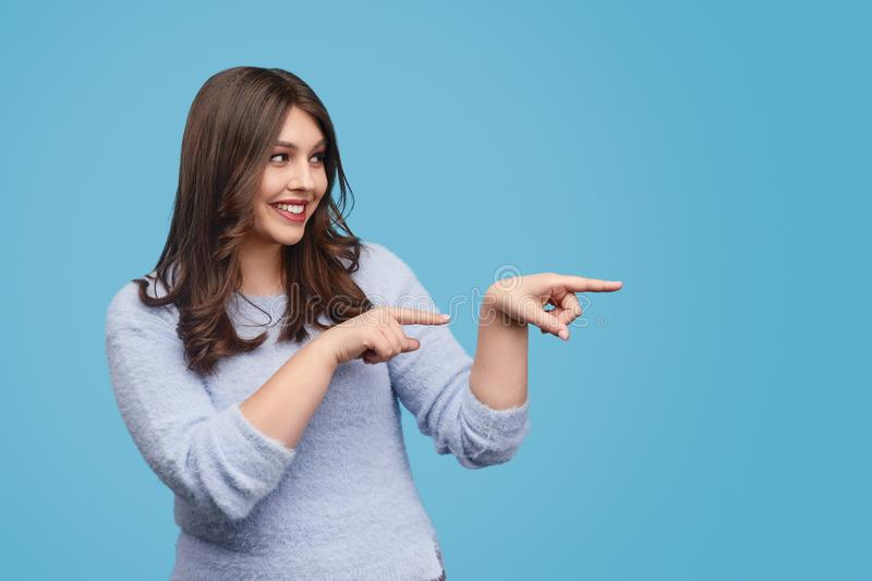 Smiling plump lady pointing at blank space royalty free stock photo