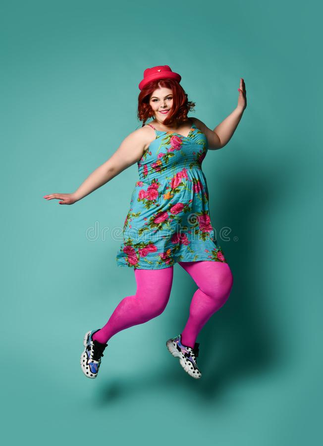 Smiling plus-size fat chubby woman in funny hat and colorful clothes jumps high or walk skipping on popular mint. Smiling plus-size fat chubby woman in funny hat royalty free stock photos
