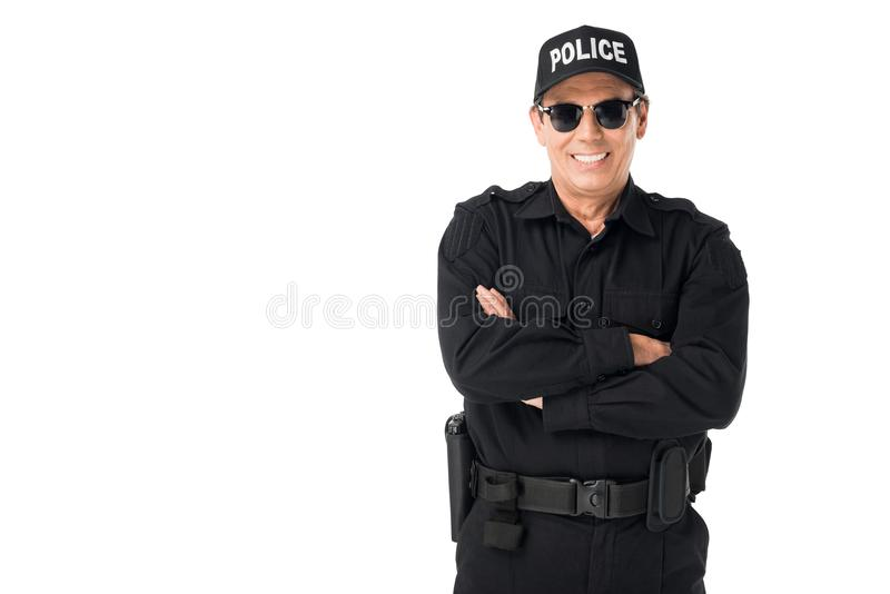 Smiling policeman wearing uniform with arms folded royalty free stock photography