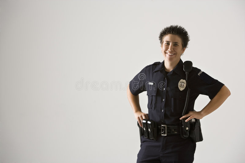 Smiling policewoman. Portrait of mid adult Caucasian policewoman standing with hands on gun holster looking at viewer smiling royalty free stock photo