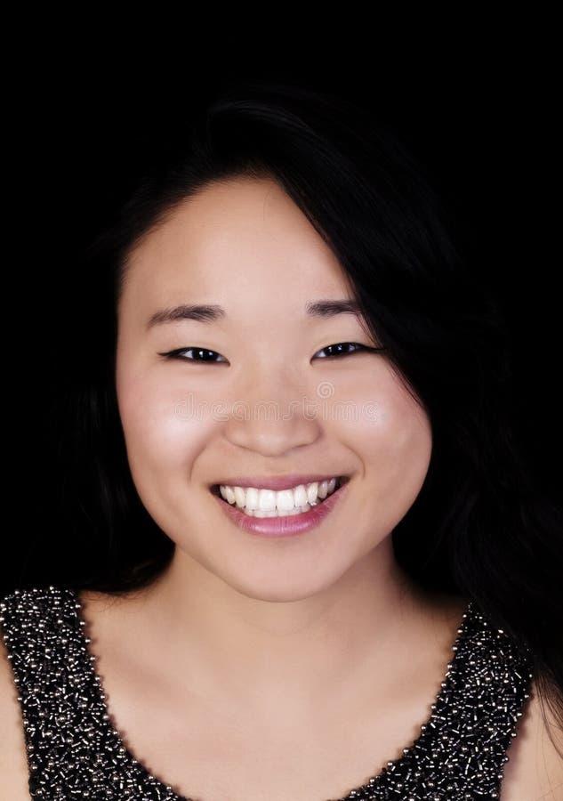 Smiling Portrait Attractive Japanese American Young Woman. Attractive Young Japanese American Woman Smiling Portrait Against Dark Background stock image