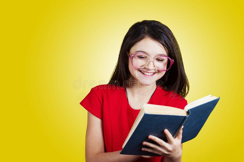 Smiling Portrait of a cute little schoolgirl loving to learn, holding with hands a book and wearing glasses royalty free stock image