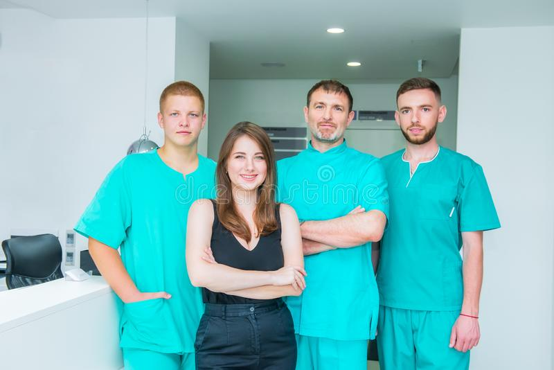 Smiling portrait team in uniform providing healthcare treatment in modern medical centre. Clinic, profession, people, health care stock photo