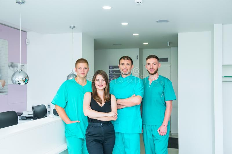 Smiling portrait team in uniform providing healthcare treatment in modern medical centre. Clinic, profession, people, health care stock images