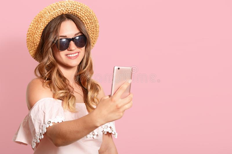 Smiling positive attractive woman stands  over pink background, making selfie, doing videocall, wearing straw hat, light royalty free stock photos