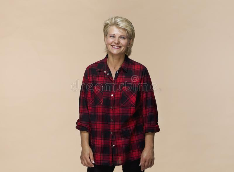 Smiling positive female with attractive look, wearing checked shirt, posing against light brown wall stock photos