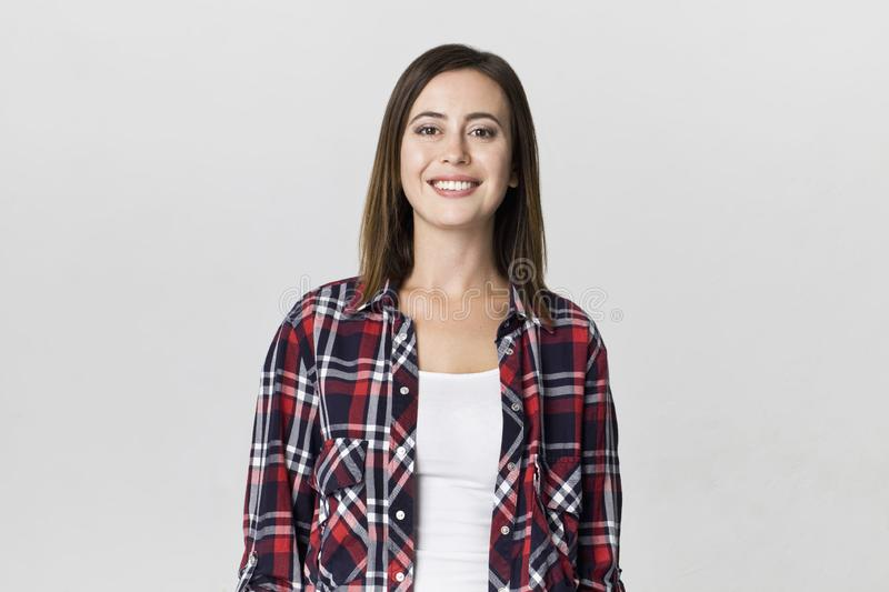 Smiling positive female with attractive look, wearing checkered shirt, posing against white blank wall stock image