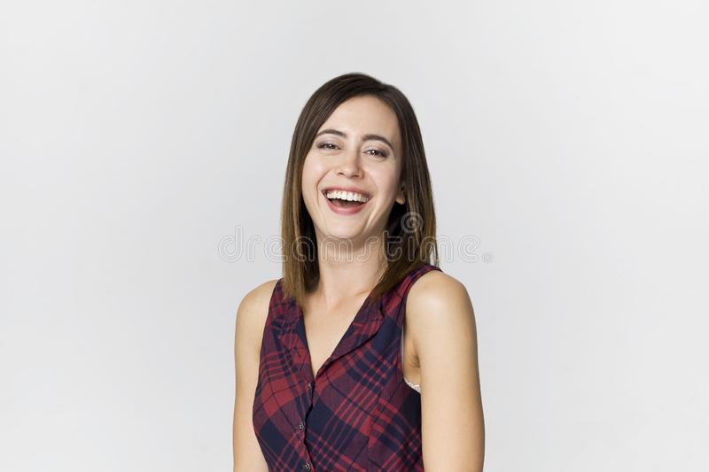 Smiling positive female with attractive look, wearing colorful dress, posing against white blank wall stock image