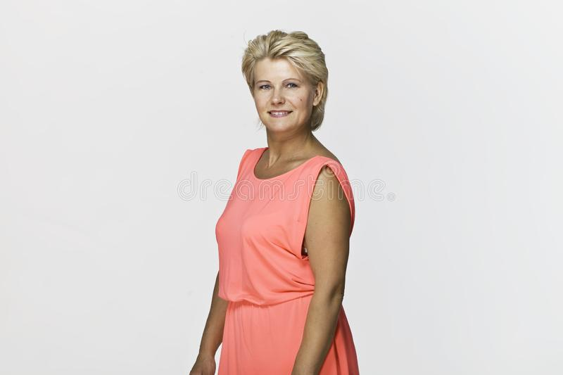 Smiling positive female with attractive look, wearing colorful dress royalty free stock photo