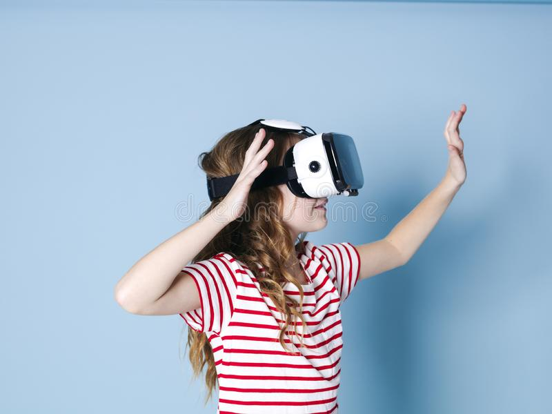 Smiling positive girl wearing virtual reality glasses goggles headset, vr box. connection, modern, new generation, concept. Girl trying to touch objects in royalty free stock photos