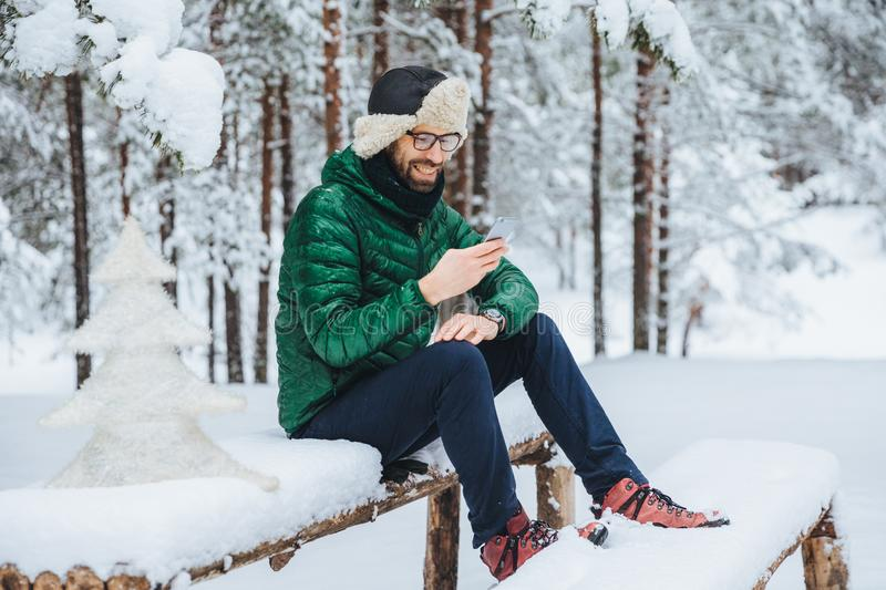 Smiling positive male wears warm winter clothes, reads message on mobile phone, spends free time in calm atmosphere outdoors in wi stock photo