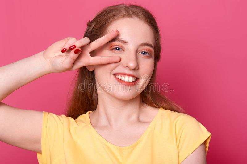 Smiling positive model poses isolated over bright pink background in studio with victory hand near her right eye, wearing yellow. Tshirt, having pleasant facial stock image