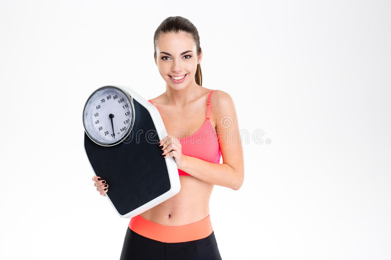 Smiling positive young fitness woman in sportwear holding weighing scale royalty free stock photography